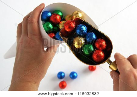 Hands Putting Colorful Candy Balls In Cone