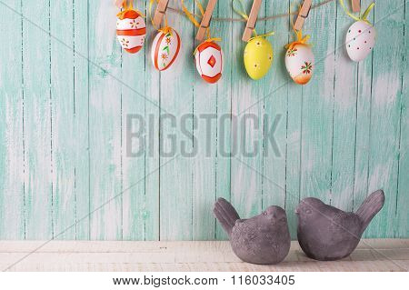 Two Decorative Birds And Colorful Easter Eggs On Rope On Wooden Background.