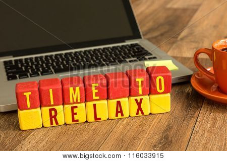 Time To Relax written on a wooden cube in a office desk