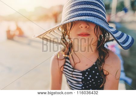 happy child in swimsuit and hat relaxing on the summer beach and getting some tan. Warm weather cozy
