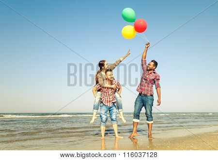 Multiracial Group Of Friends Have Fun Playing Piggyback On The Beach