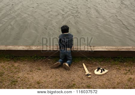 Boy With Wooden Sword Is Looking On The River.