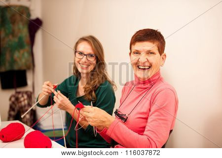 Women Knitting With Red Wool. Eldery Woman Transfering Her Knowledge Of Knitting On A Younger Woman