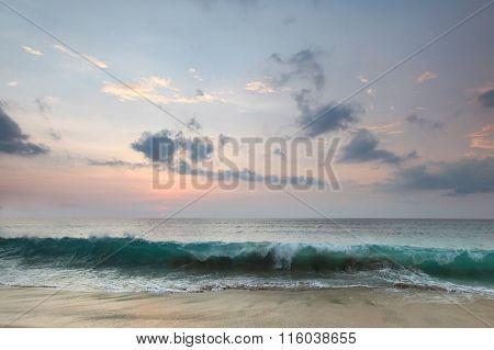 Beautiful Bali sunset with reflection in beach sand