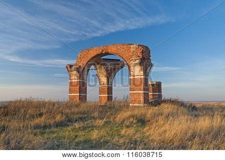 Brick arches of old church ruins solitary in the field
