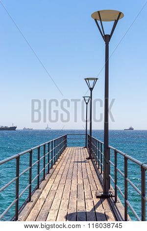 Vanishing pier with lamp and rails against view on ships and oil platform on Mediterranean Sea
