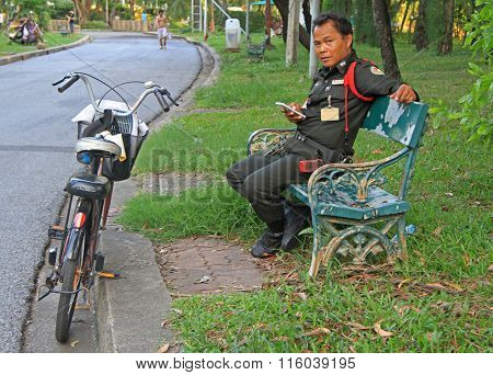 police officer is resting on a bench in Bangkok, Thailand
