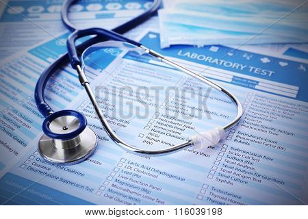 Stethoscope and medical mask on laboratory test lists, close up