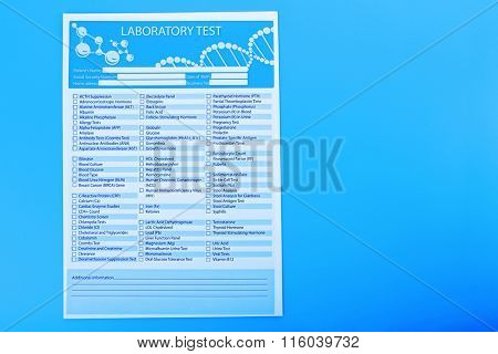 Laboratory test list on blue background, close up