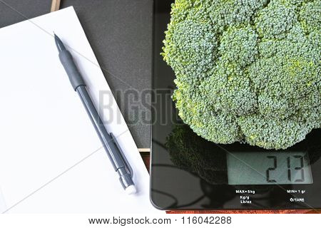 Weight control - kitchen scale with green broccoli, pencil and paper