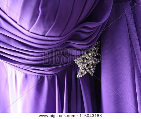 Bridesmaid dress in purple with a diamond accent. Flowing pleats pulls the belt-line inward. The added bling pulls the eye toward the new waistline.