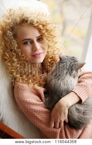 Young woman and cat beside window in the room