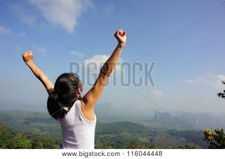 cheering young woman open arms  on mountian peak
