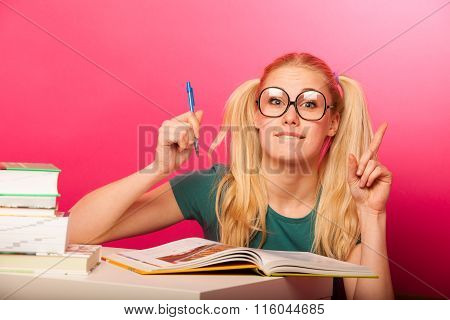 Courious, Playful Schoolgirl With Two Hair Tails Sitting On Floor Behind The Small Table Full Of Boo
