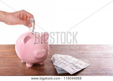 Man putting dollar banknotes in pig moneybox