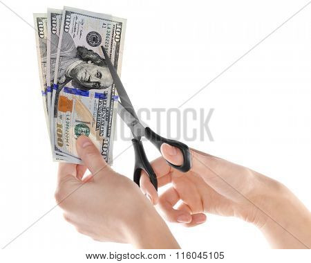 Hands with scissors cutting dollar banknotes, isolated on white