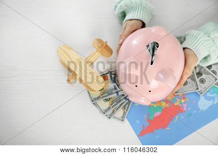 Woman holding piggy bank with inserted dollar banknote. Savings money for travel concept