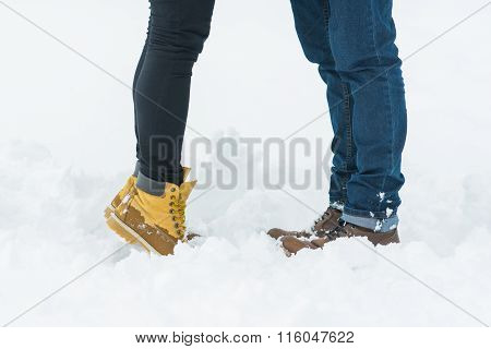 Young couple in winter boots standing on snow