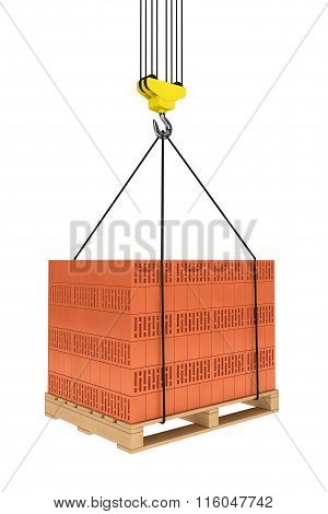 Tower Crane Hook With Stacked Red Bricks Over Wooden Pallet