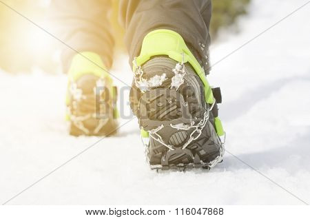 Hiking boots with equipment for ice. Snow like a background and sun. Sun is shining. Moutains