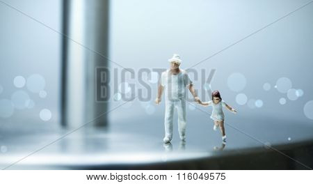 Miniature people -  a father walking with her daughter