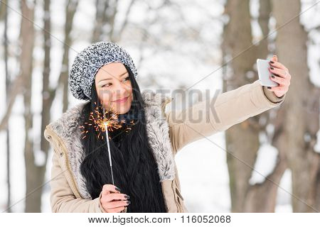 Young woman taking a selfie in park in winter holing a sparkler