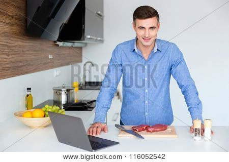Portrait of attractive man in blue shit with laptop preparing meat on the kitchen