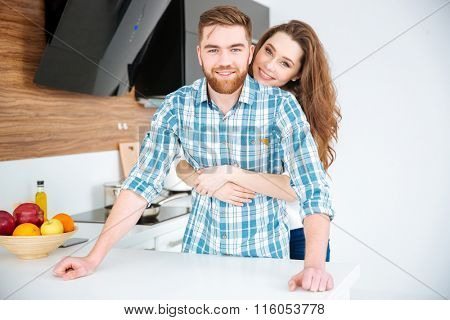 Portrait of a smiling young couple hugging in the kitchen at home