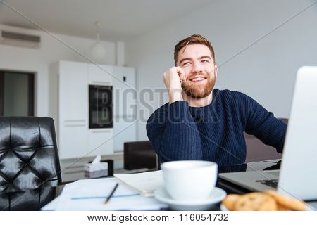 Smiling sitting at the table with laptop and talking on the phone at home