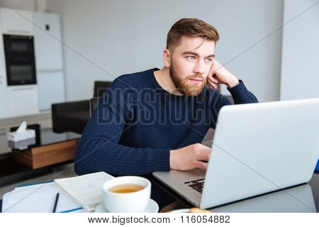 Portrait of a pensive man sitting at the table with laptop computer at home