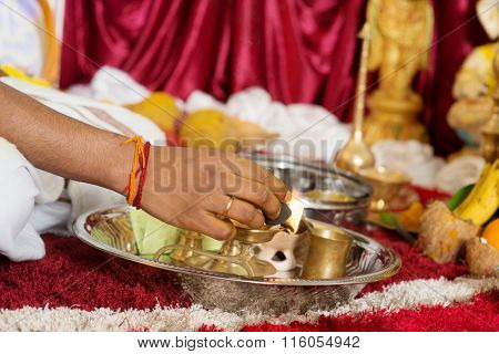 Traditional Indian Hindu religious praying items in ear piercing ceremony for children. Focus on the hand and oil lamp. India special rituals heritage.