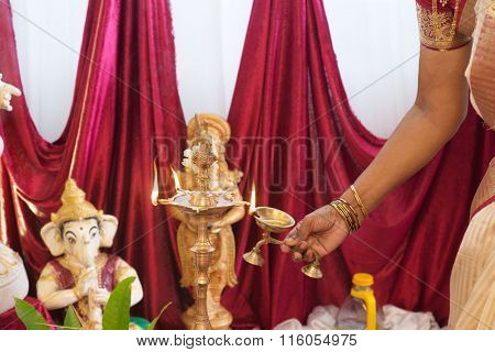 Woman hand lighting up the metal diya. Traditional Indian Hindus religious ceremony. Focus on the oil lamp. India special rituals events.