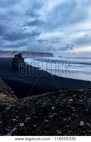 Rock on black sand beach