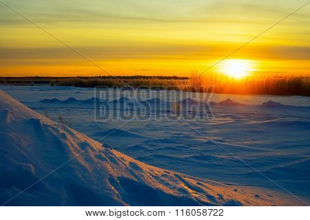Bright Sun At Sunset In Winter With Large Snow Drifts.