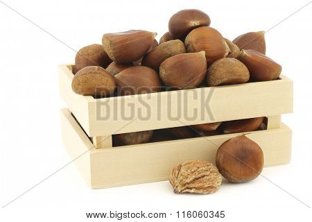 chestnuts and a peeled one in a wooden box on a white background