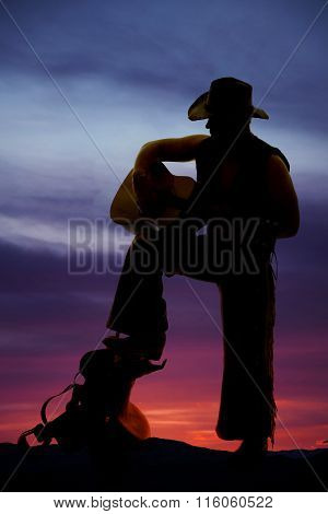 Silhouette Of Cowboy Foot On Saddle Guitar Play