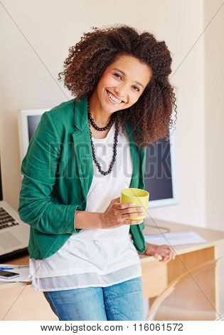 Young mixed race businesswoman smiling with a cup of coffee