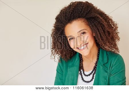 Mixed race businesswoman with a curly afro smiling warmly
