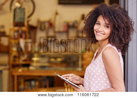 Mixed race woman standing in the door of her cafe