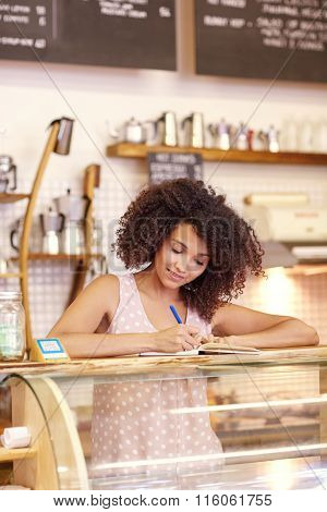 Young woman with afro at coffee counter writing an order