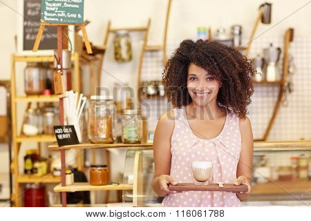 Beautiful waitress bringing a latte on wooden tray in cafe