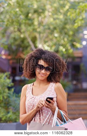 Woman in sunglasses sending a message on her phone