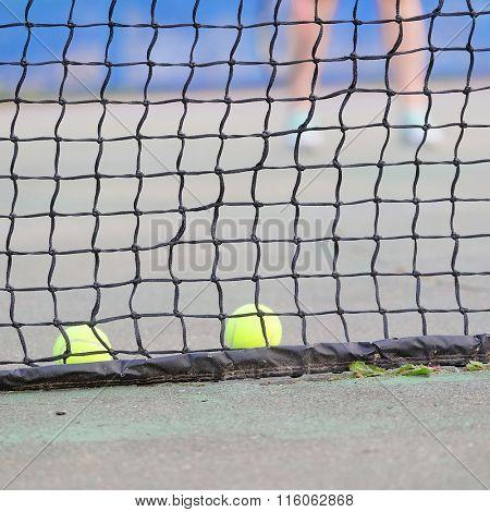 Tennis balls lies near the tennis net