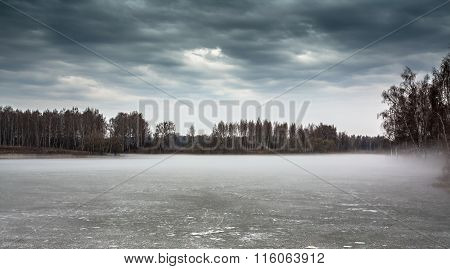 Gloomy landscape on frozen misty lake in season between winter and spring