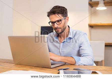 Young casual office worker working on laptop. Young businessman typing on laptop computer at office. Young man working absorbed on laptop at work place.