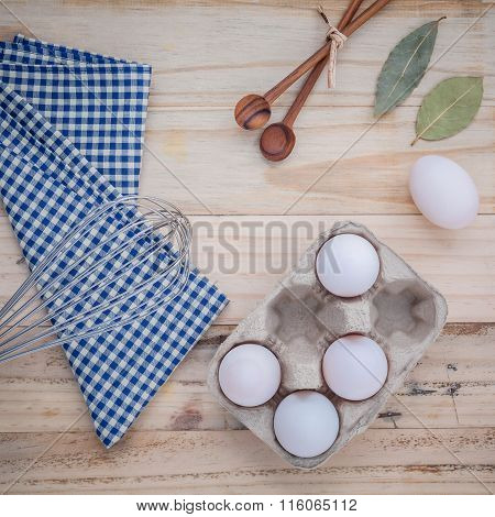 Cardboard Egg Box With Eggs ,pepper Bottle ,wooden Spoons ,bay Leaf And Wire Whisk Set Up On Old Woo
