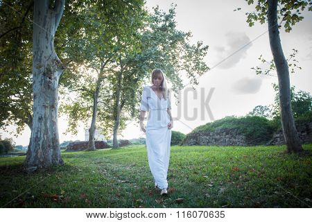 woman in long white dress walk among trees in park, natural light, full body shot