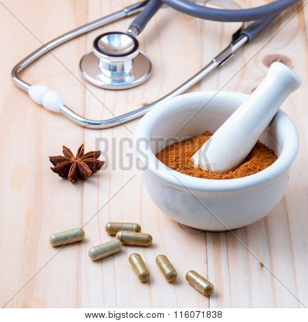 Alternative Health Care  Chinese Herbs Powder In The White Mortar And Herbs Capsule  On Old Wooden B