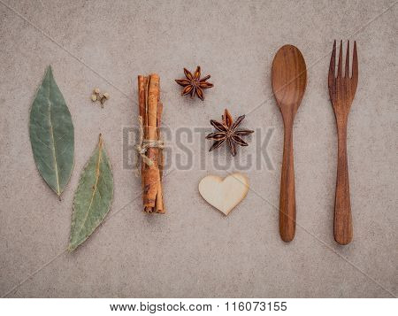 Wooden Spoon ,fork ,cinnamon ,star Anise ,wooden Heart And Bay Leaves Set Up On Brown Paper Board Co