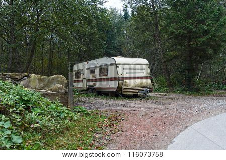 Old Trailer Is In The Woods Near The Road